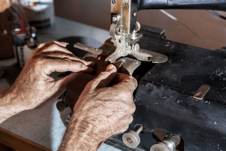 Cropped Image Of Wrinkled Hands Sewing Textile On Machine