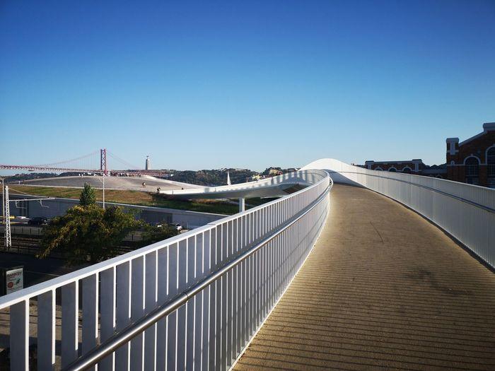 Footbridge over city against clear blue sky