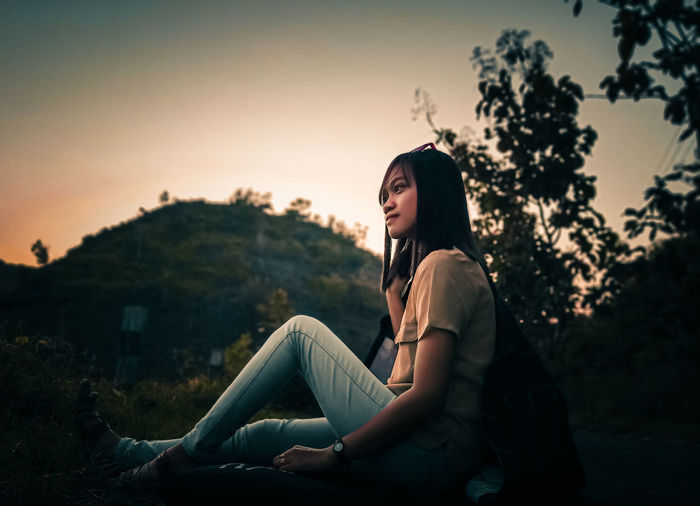 Side view of woman sitting against sky during sunset