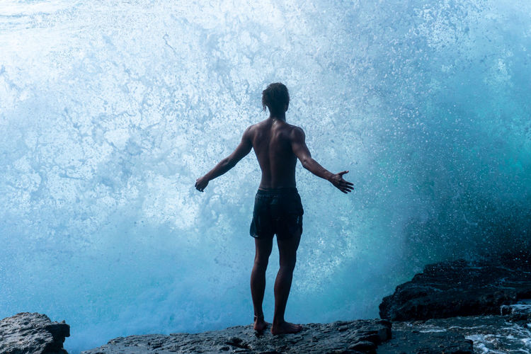 Rear view of shirtless man standing on rocks against waves