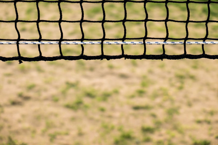 Close-up of volleyball net at beach