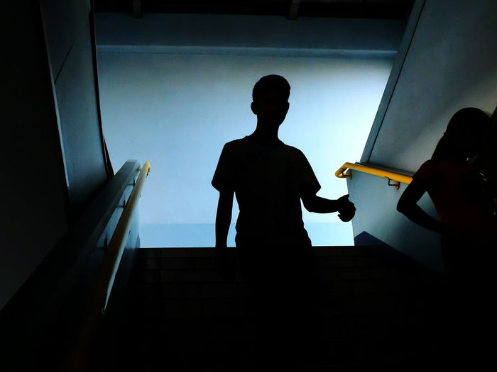 Silhouette man walking down stairs at subway