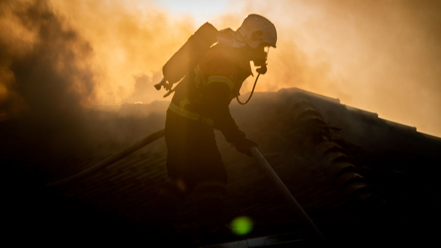 Side view of firefighter holding hose during sunset