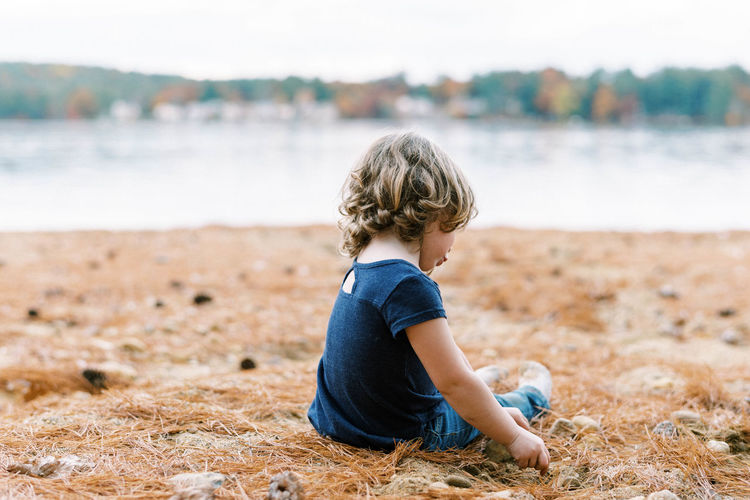 Side view of boy sitting on beach