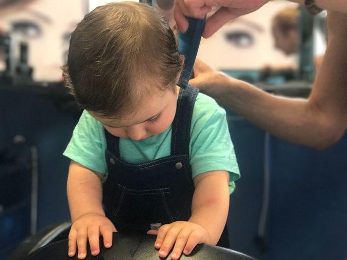 Baby boy having haircut in salon