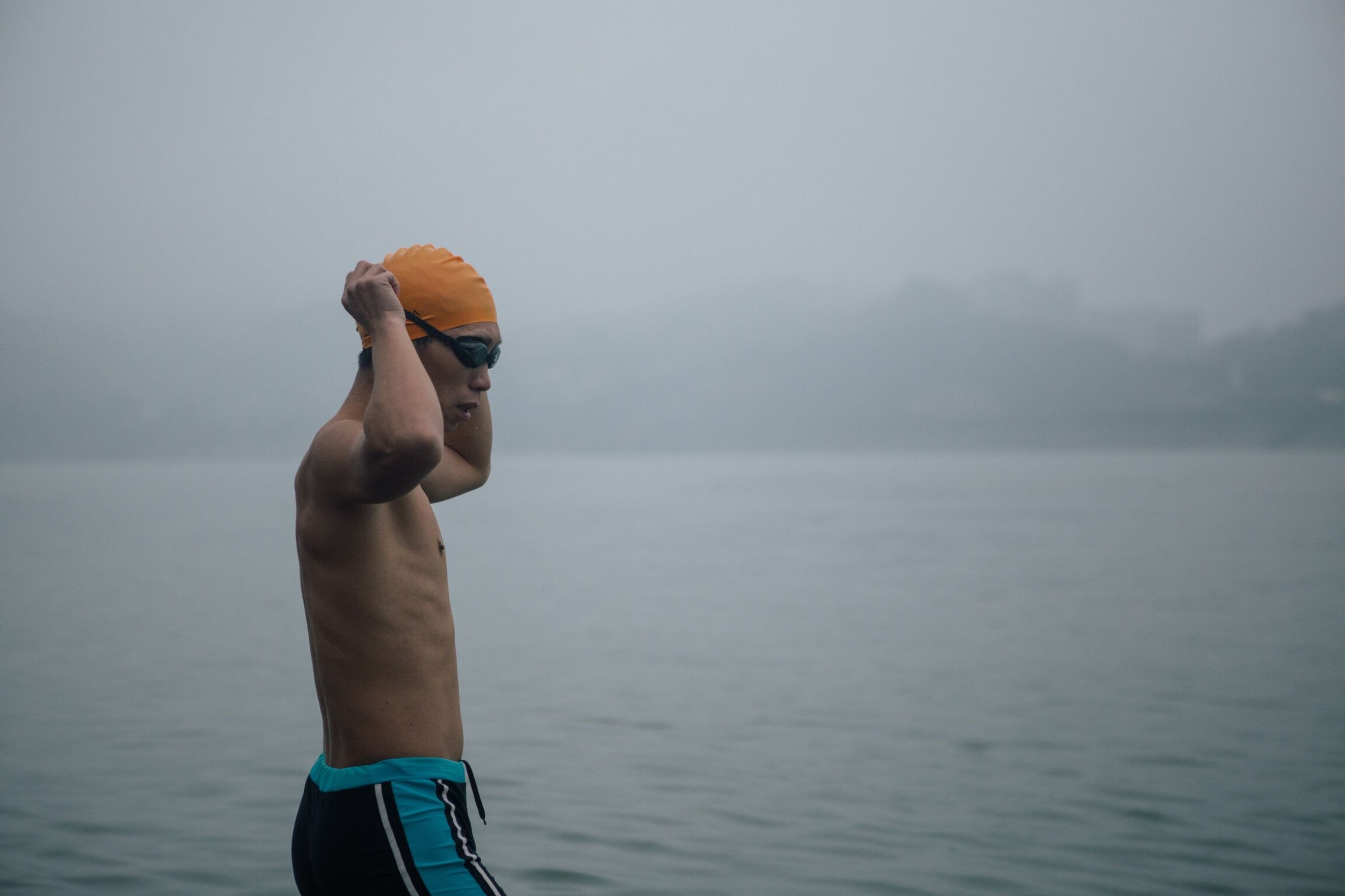 water, sea, shirtless, side view, real people, lifestyles, one person, athlete, men, day, focus on foreground, standing, sports clothing, sky, outdoors, beard, sportsman, leisure activity, only men, young adult, fog, horizon over water, nature, one man only, adults only, adult, people