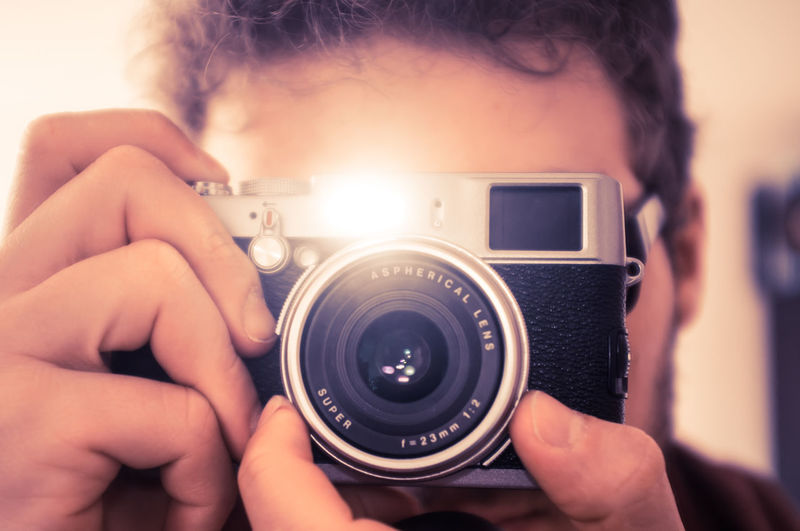 Close-up of man photographing through camera
