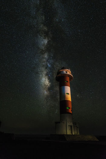 Low angle view of lighthouse against sky at night