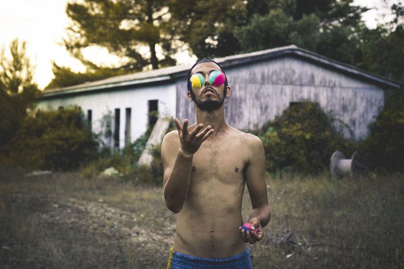 Shirtless Young Man Juggling Multi Colored Balls In Yard