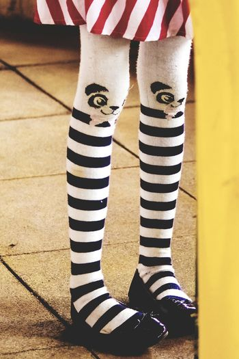 Low Section Of Girl Wearing Striped Panda Sock