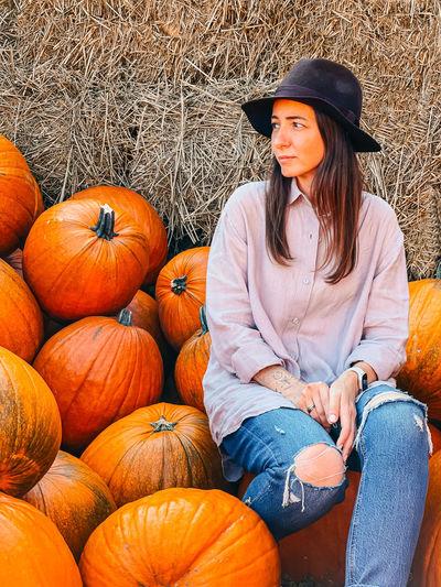 Full length of smiling man sitting by pumpkin