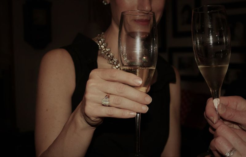 Midsection of friends holding champagne