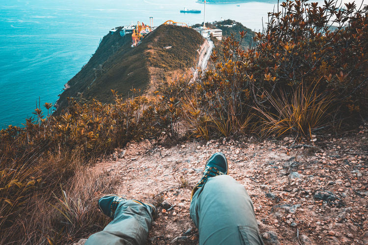 Man resting on the hiking trail at brick hill nam long shan that overlooks ocean park, hong kong