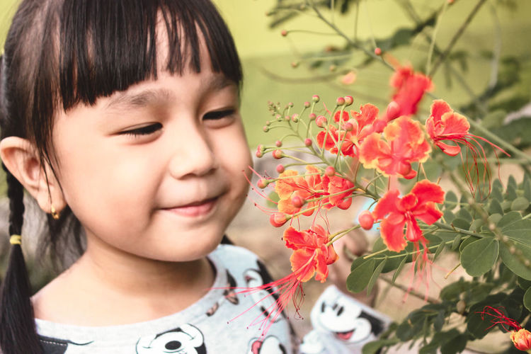Close-up portrait of cute girl with pink flower