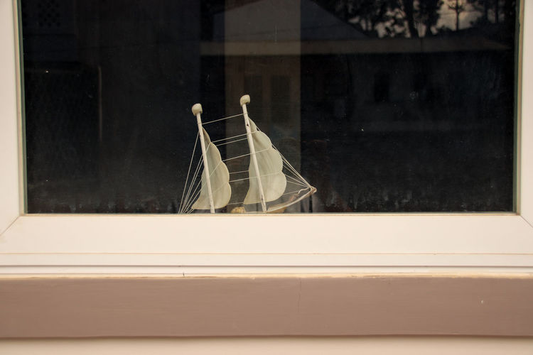 Close-up of toy boat at a window sill at home
