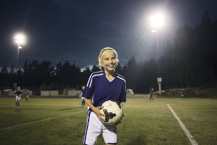 Portrait of smiling young woman on soccer field against sky
