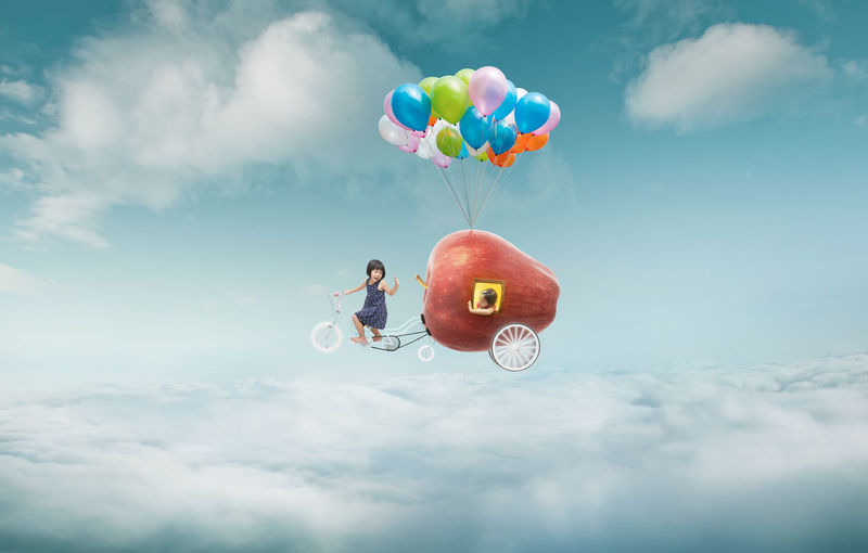 Girl riding vehicle on cloudy sky
