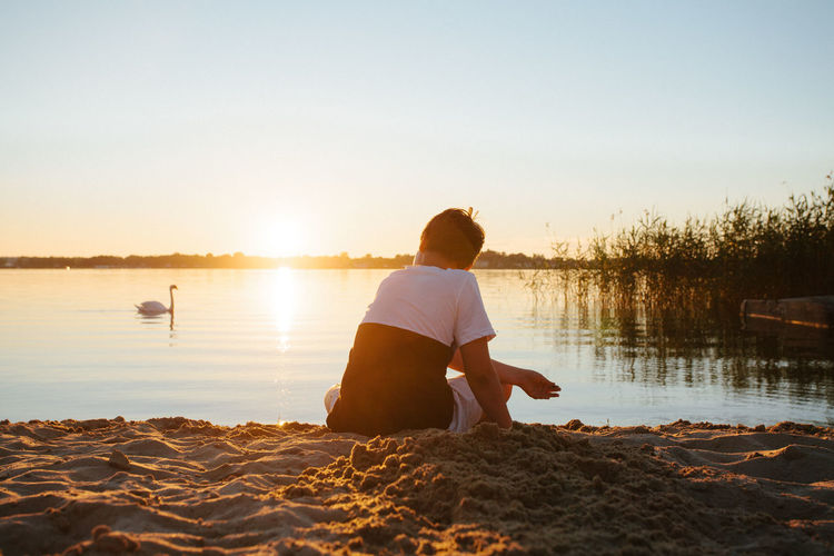 Rear view of man sitting at beach against sky during sunset