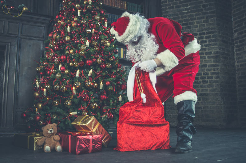 Man wearing santa claus costume holding christmas present at home