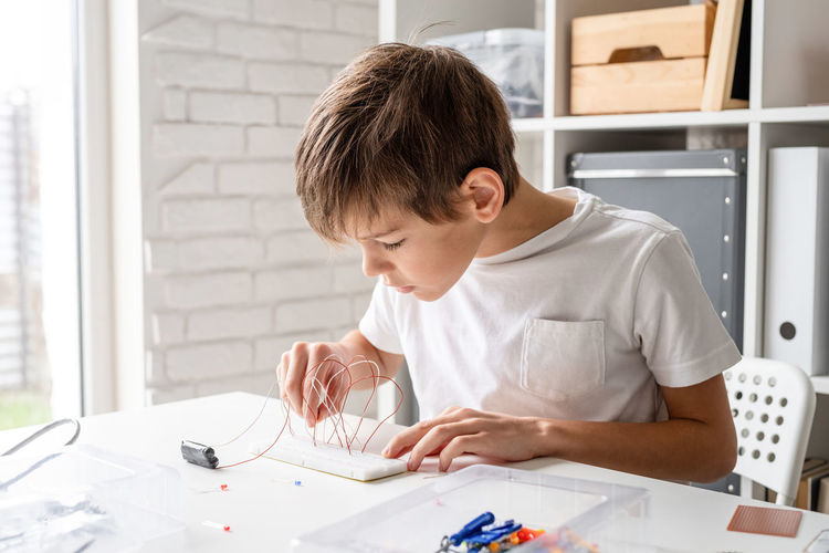 Boy hands working with led lights on experimental board for science project