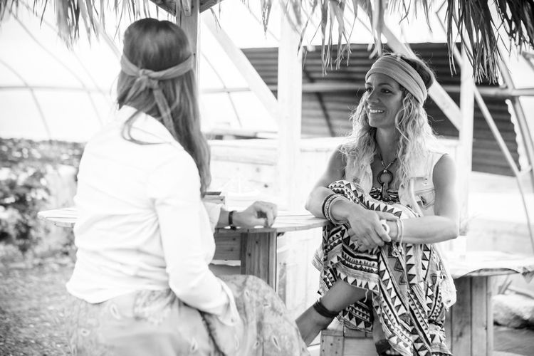 Black and white portrait of young hippy girls enjoying the friendship together sit down at a rural country bar - smile and happiness with alternative lifestyle Women Real People Three Quarter Length Leisure Activity Lifestyles Two People Long Hair Females Young Adult Hairstyle Focus On Foreground Adult Casual Clothing Hair Girls People Day Young Women Bonding Outdoors Teenager Beautiful Woman Caucasian Smiling Happiness person Hippie Togetherness Sitting Fashion Females Summer Retro Styled Vacations Positive Emotion Indie Rock