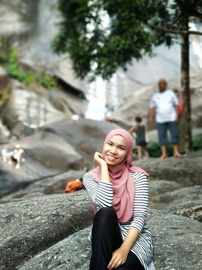 Happy Hiking Jungle Trekking Travel Destinations Travel Hijab Headwear Rock Waterfall Nature Young Women Women Smiling Sitting Portrait Happiness Enjoyment Beautiful Woman Full Length Tourism Tourist Attraction