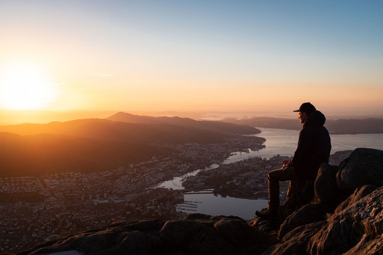 Man sitting on rock against sky at sunset