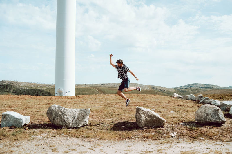 Man jumping on rock against sky