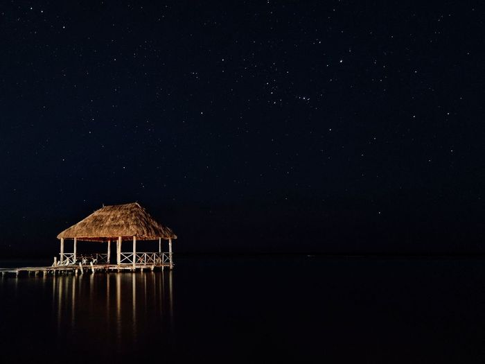 House on lake against sky at night