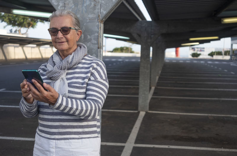 Smiling senior woman using smart phone while standing in parking lot
