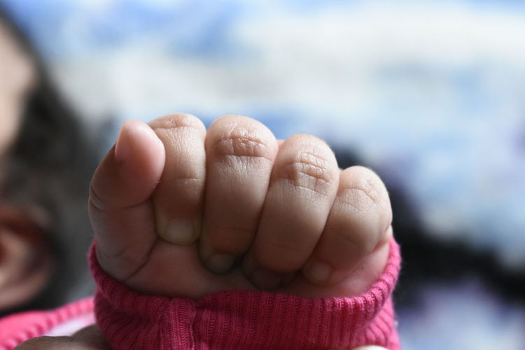 Close-up of baby with clenching fist