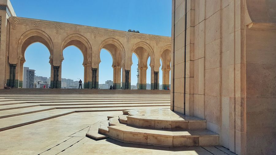 Hassan II Mosque Hassan Mosque 2 Architecture Built Structure Building Exterior Arch City Shadow Architectural Column Clear Sky Travel Destinations Colonnade Narrow Column Blue History Outdoors Arcade Day Sky Corridor City Life Casablanca, Morocco