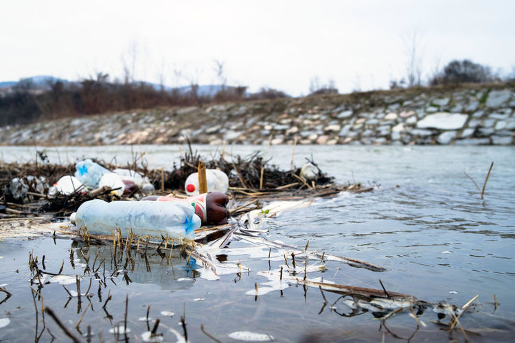 Man working on garbage by river against sky
