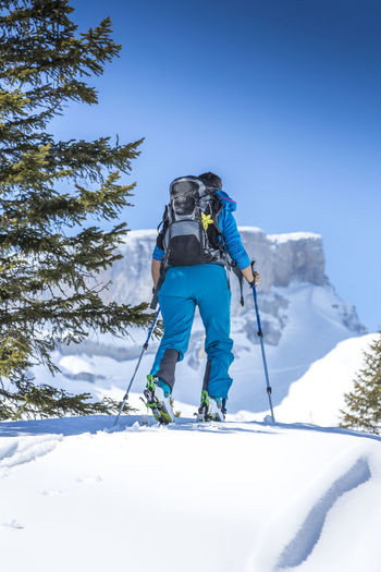 Rear view of woman skiing on snow covered field during winter