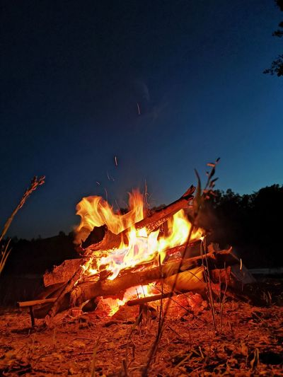 Low angle view of bonfire on field against sky at night