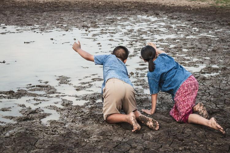 Siblings playing at muddy lakeshore