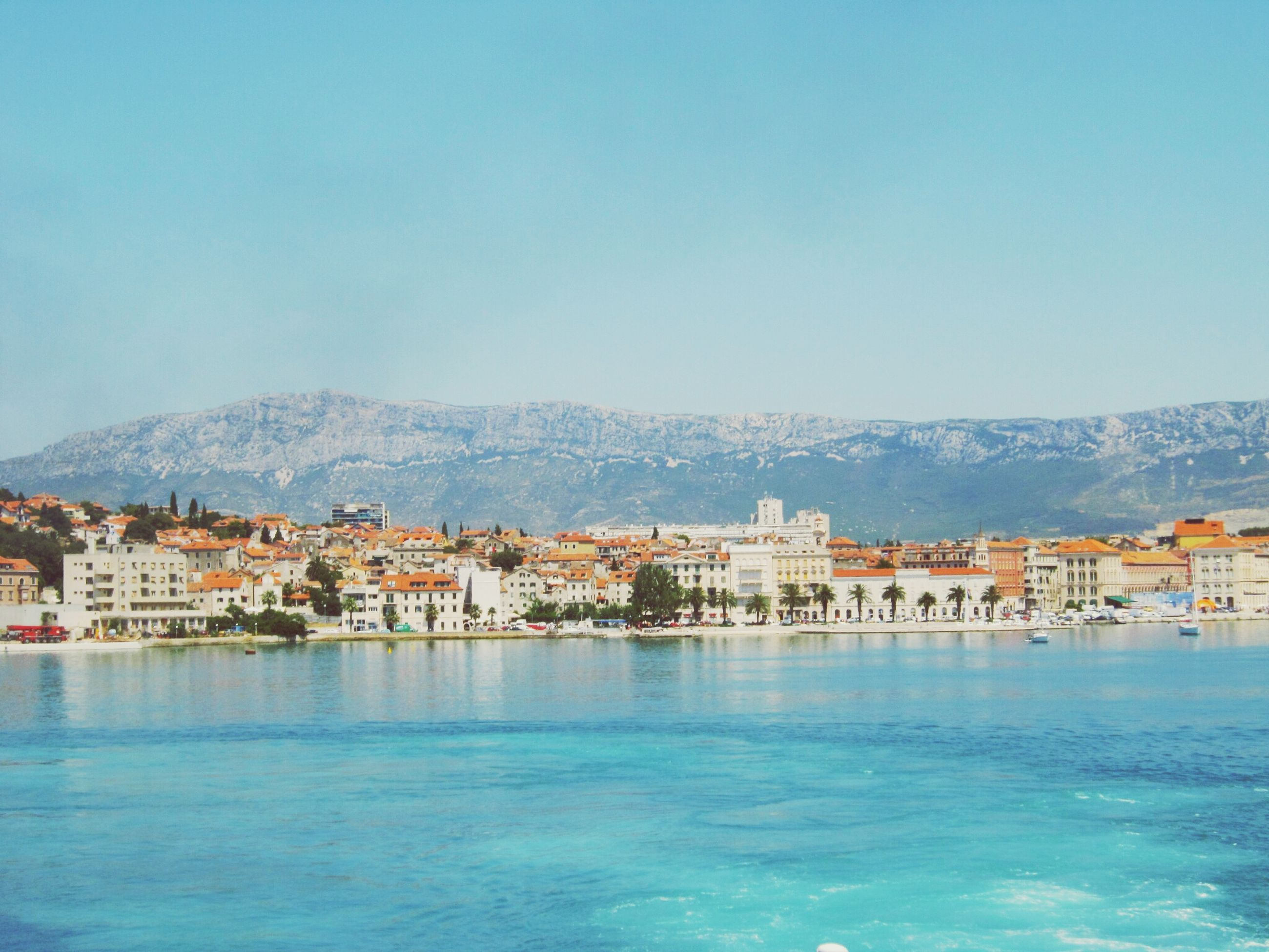 water, building exterior, architecture, built structure, clear sky, blue, waterfront, copy space, mountain, sea, house, residential structure, residential building, town, residential district, scenics, day, nature, tranquil scene, tranquility