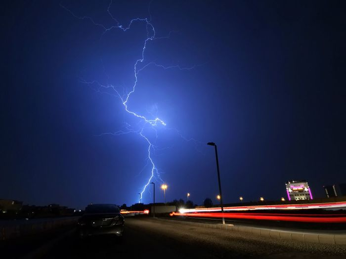 Lightning over road against sky at night