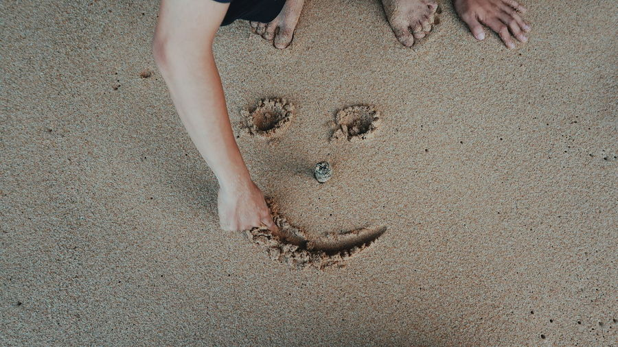Low section of man making anthropomorphic smiley face in sand at beach