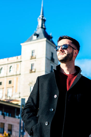 Handsome man wearing sunglasses against building in city