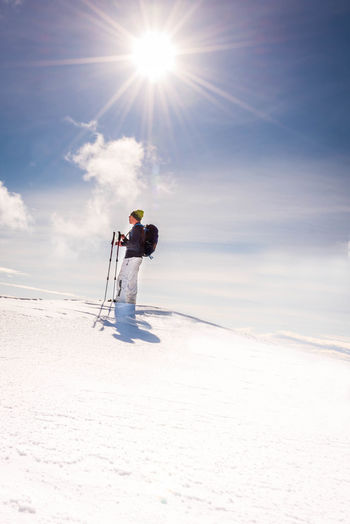 Low angle view of man standing on snow covered land against sky