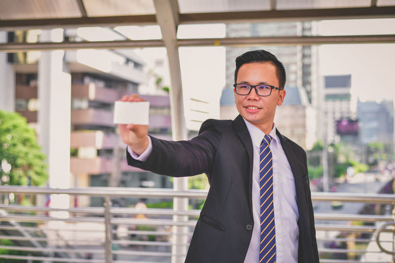 Young businessman holding business card while standing against buildings in city