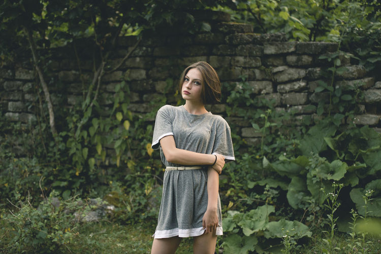 Portrait of young woman standing against plants and wall