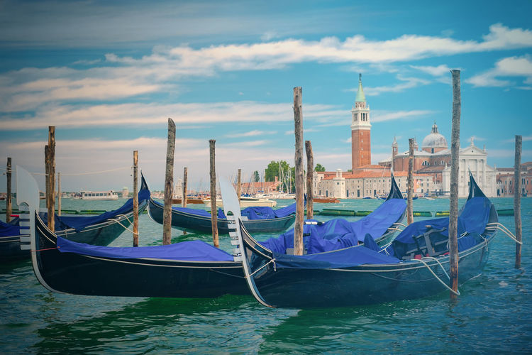 Gondolas moored on canal against church of san giorgio maggiore