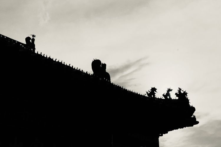 Low angle view of silhouette building on roof against sky