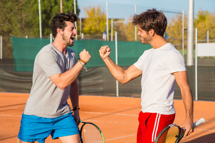 Two friends standing on tennis court and encouraging each other before match. Adult Athletic Court Friends Happy Lifestyle Active Activity Attractive Cheerful Encouragement Enjoying Friendship Gesture Handsome Joy Match People Players Professional Smiling Sport Sportwear Strength Tennis 🎾