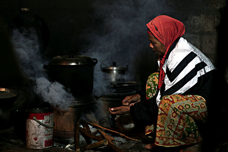 Side View Of Senior Woman Cooking Food