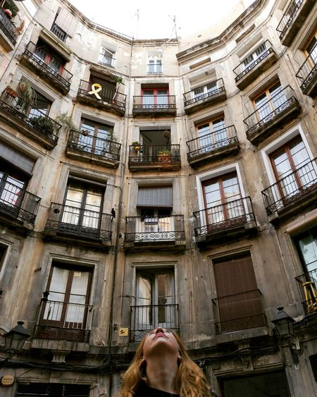 Apartment Arch Architecture Balcony Building Building Exterior Built Structure City Day Headshot Human Body Part Leisure Activity Lifestyles Low Angle View One Person Outdoors Real People Residential District Window Women