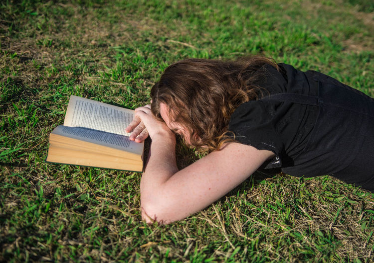 Young woman lying down in the grass with a book. One Person Nature White Woman Young Adult Portrait Curly Hair Freckles Black Dress Caucasian Candid Real People Smart Intelligent Intelligence Lifestyle Reading Green Outdoors Tranquility Sunny Day Beautiful Book Grass Land Relaxation Day Boring Bored Boredom Studying Learning