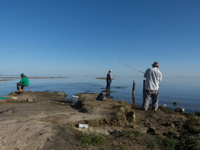 People fishing at beach against clear sky